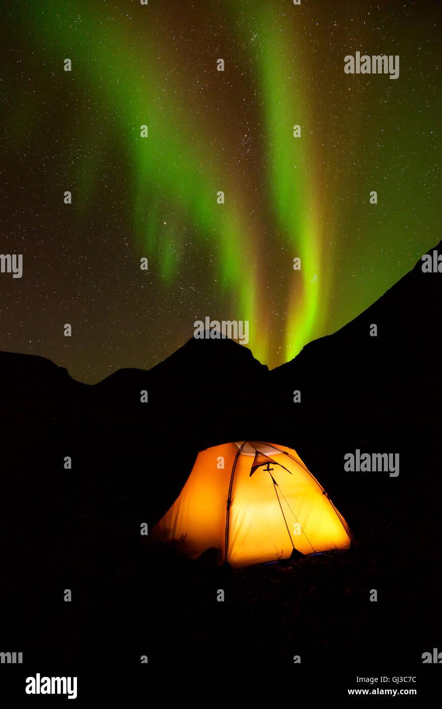 Illuminated tent and Aurora borealis at night, Khibiny mountains, Kola Peninsula, Russia - Stock Image