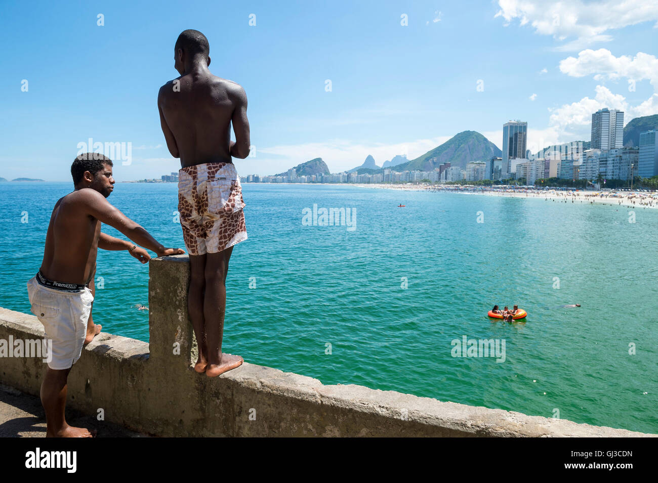 RIO DE JANEIRO - FEBRUARY 27, 2016: Young Brazilians gather to dive from the ledge at Leme, at the far end of Copacabana - Stock Image