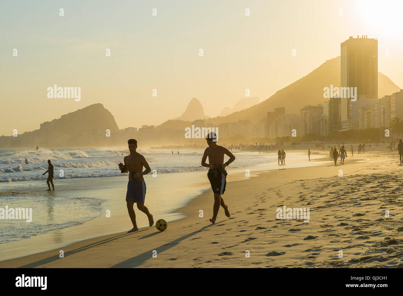 RIO DE JANEIRO - OCTOBER 30, 2015: Young carioca Brazilian men run kicking a football soccer ball along Copacabana - Stock Image