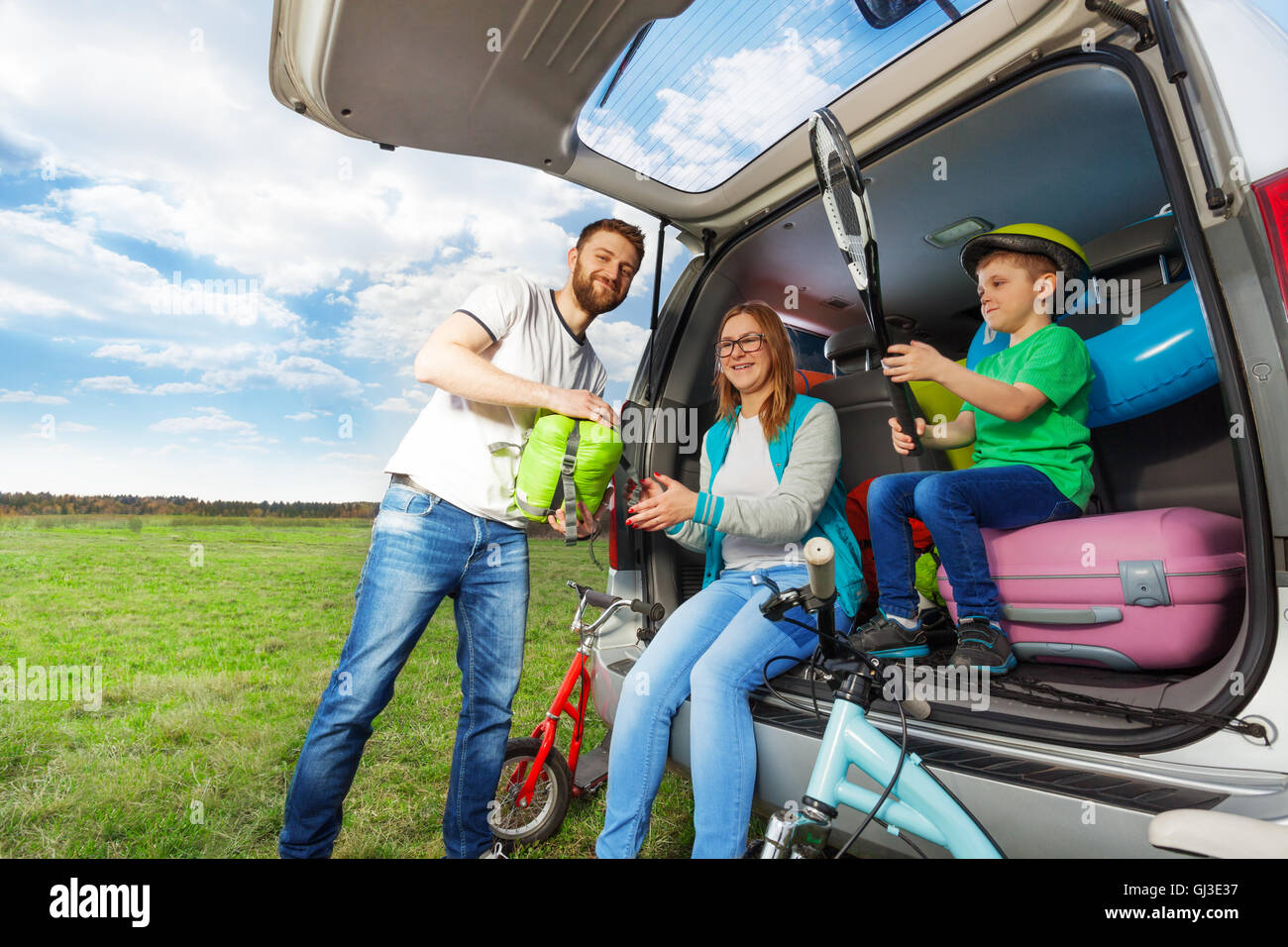 Young family loading luggage boot for the car trip - Stock Image