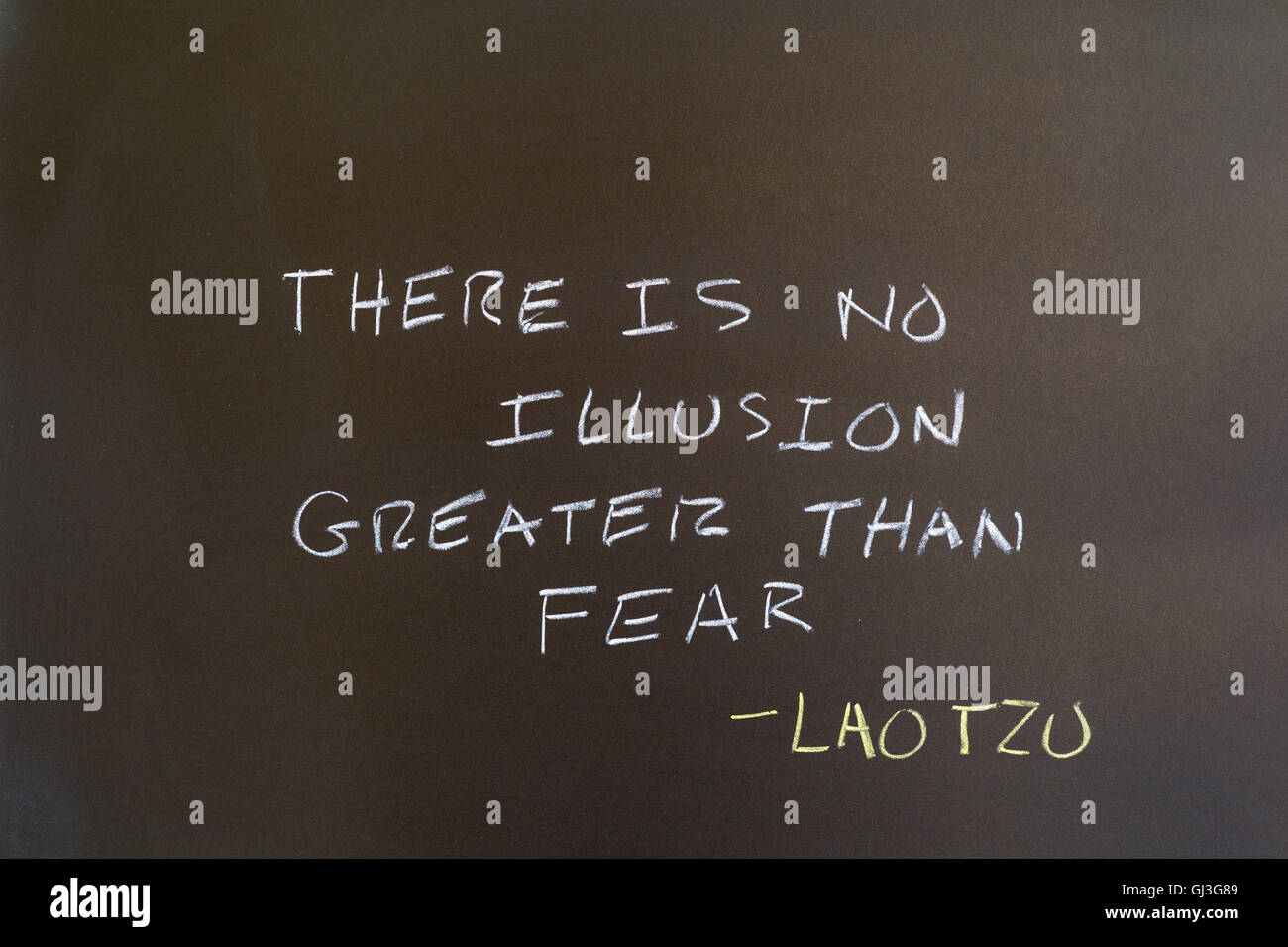 Quote by Lao Tzu. 'There is no illusion greater than fear.' Written on chalkboard. - Stock Image