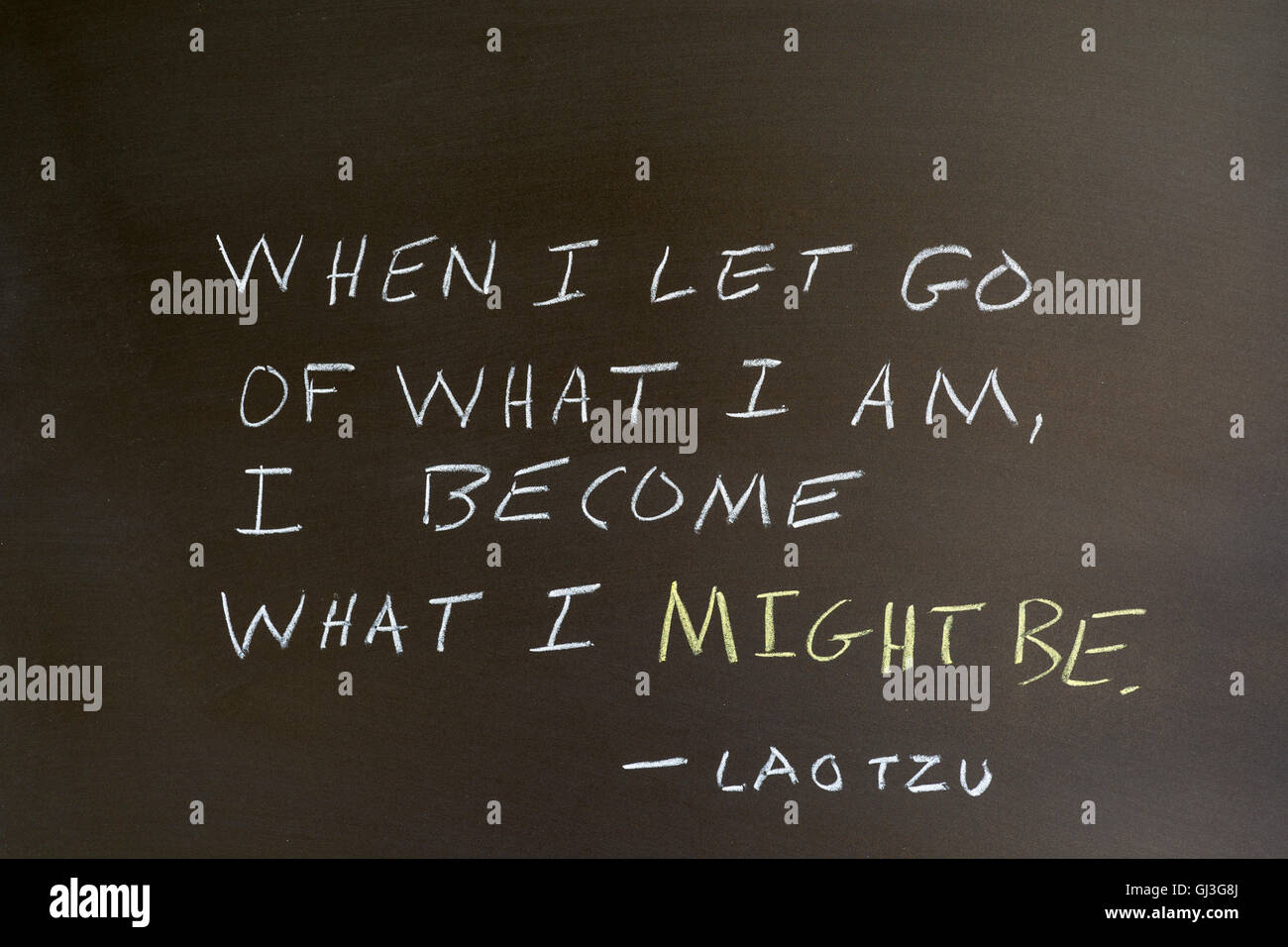 Quote by Lao Tzu. 'When I let go of what I am, I become what I might be' Written on chalkboard. - Stock Image