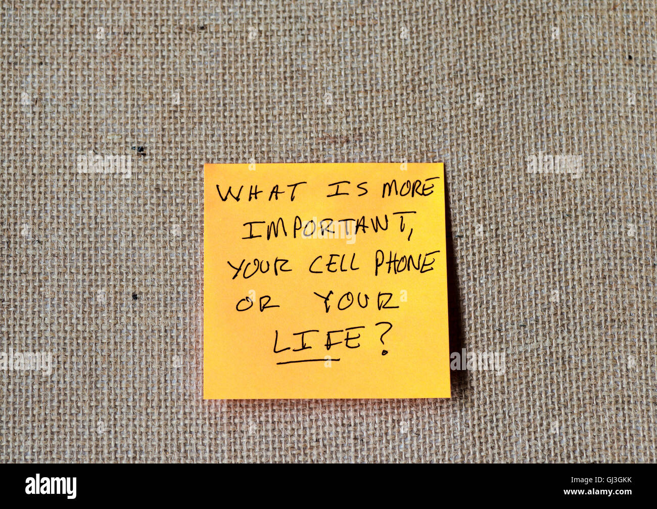 phrase 'what is more important, your cell phone or your life?' written on sticky notes - Stock Image