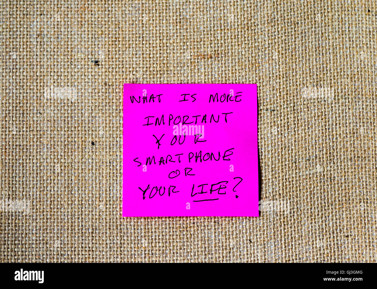 phrase 'what is more important, your smartphone or your life?' written on sticky notes - Stock Image