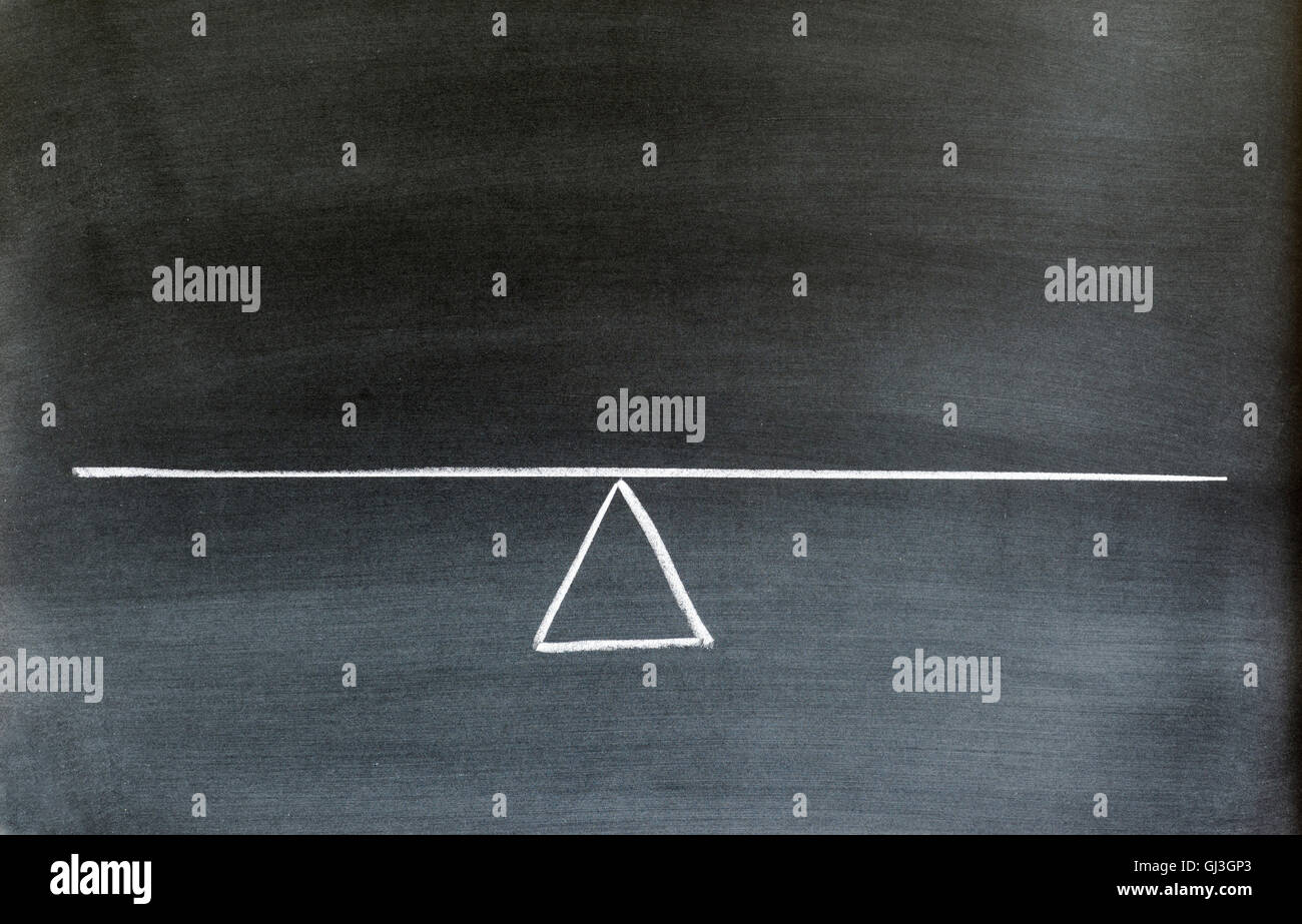 seesaw or scale in equilibrium drawn on chalkboard. Stock Photo
