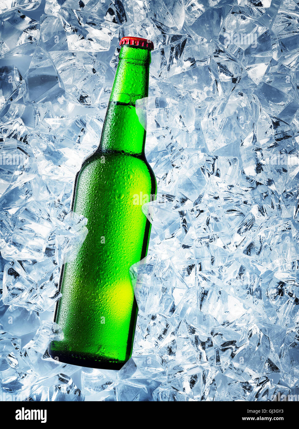 Green bottle of beer with drops on ice cubes Stock Photo