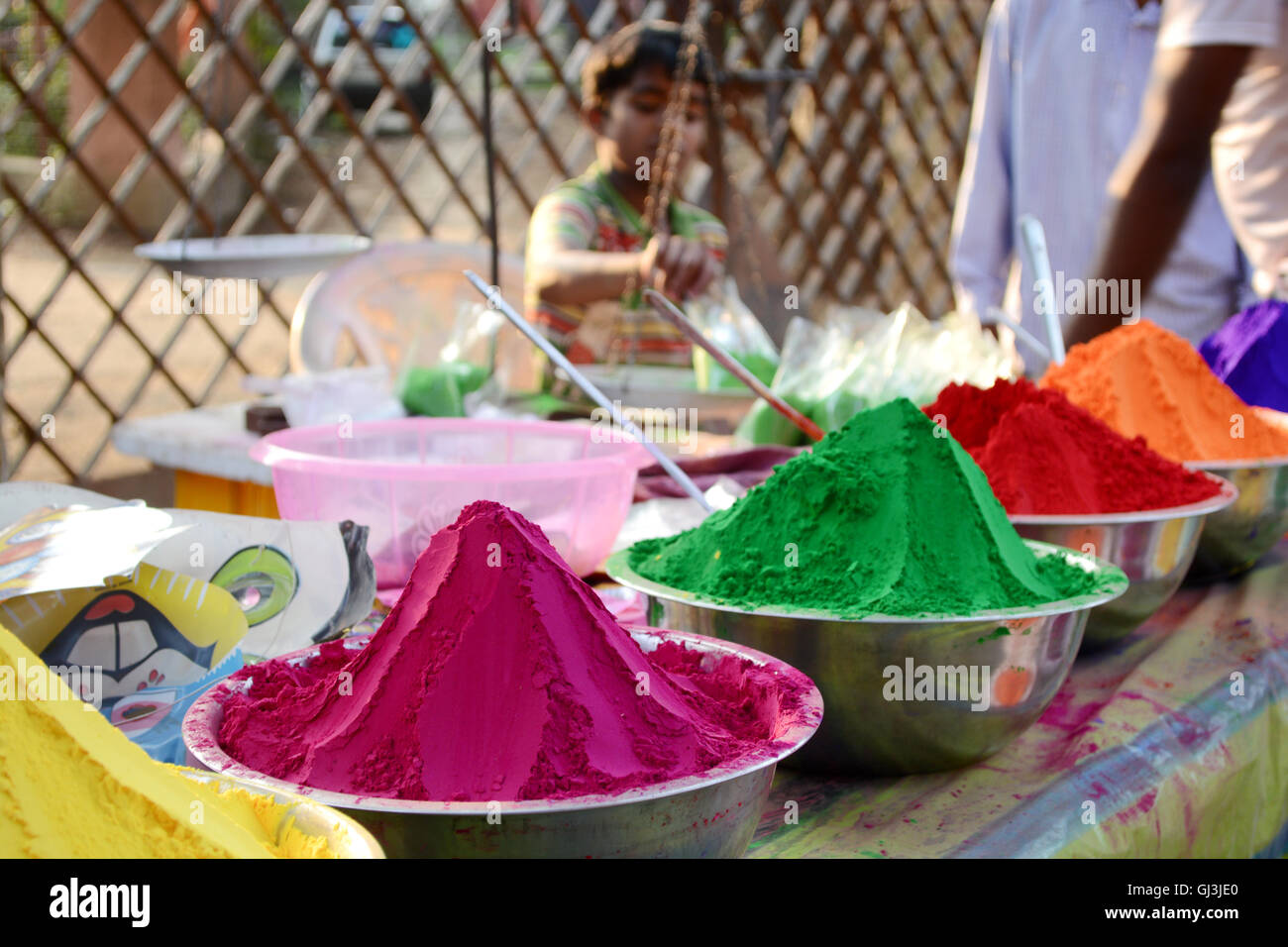 Colors of India. A boy is selling colorful powder in the market. Child labor. - Stock Image