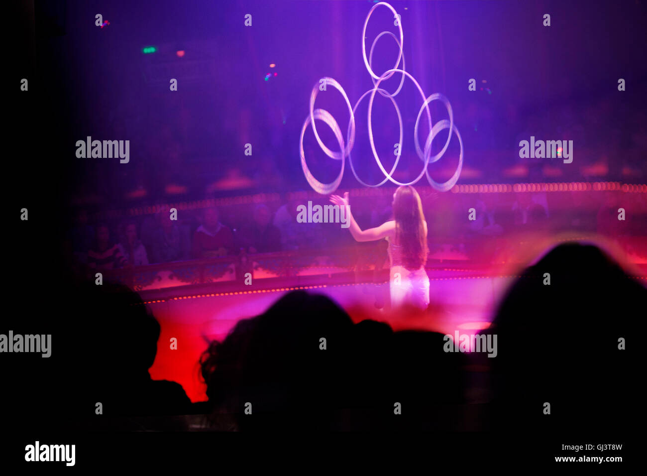 Artiste (female) with hoops in circus ring with audience - Stock Image