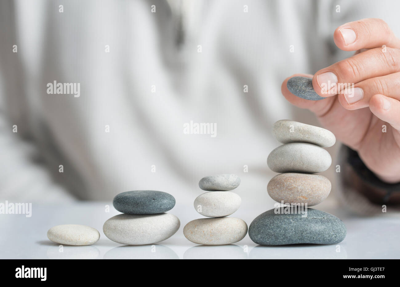 Horizontal image of a man stacking pebbles on a table with copyspace for text. Concept of risk management and wealth. - Stock Image