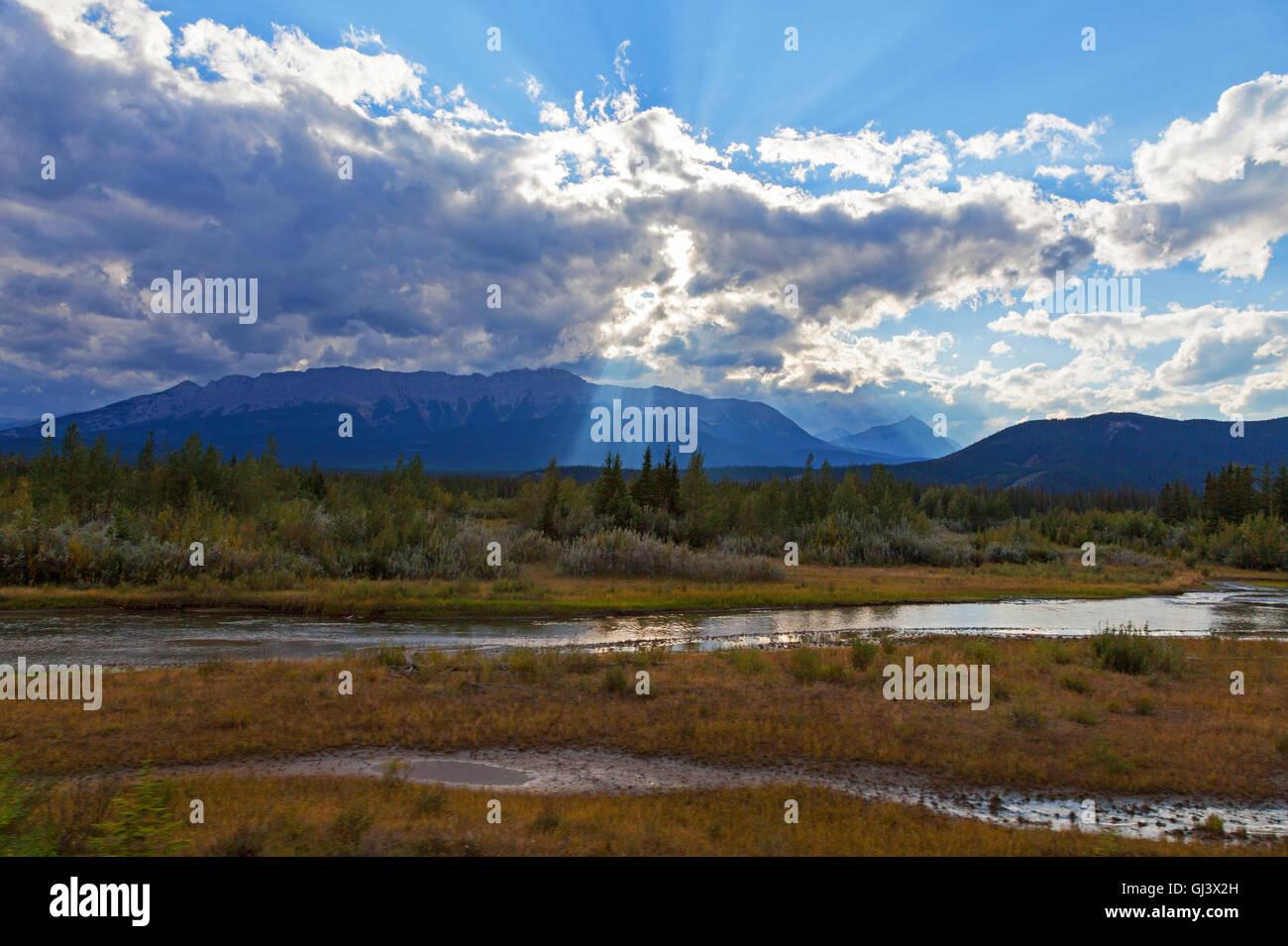 sunbeams shining through a cloudy sky over the Althabasca River Jasper Alberta Canada - Stock Image