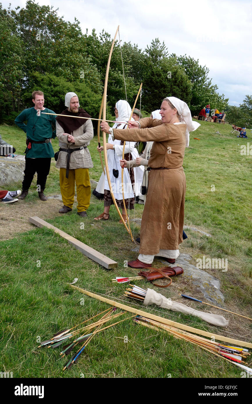 Medieval re enactment. Middle aged woman shoots a longbow. - Stock Image