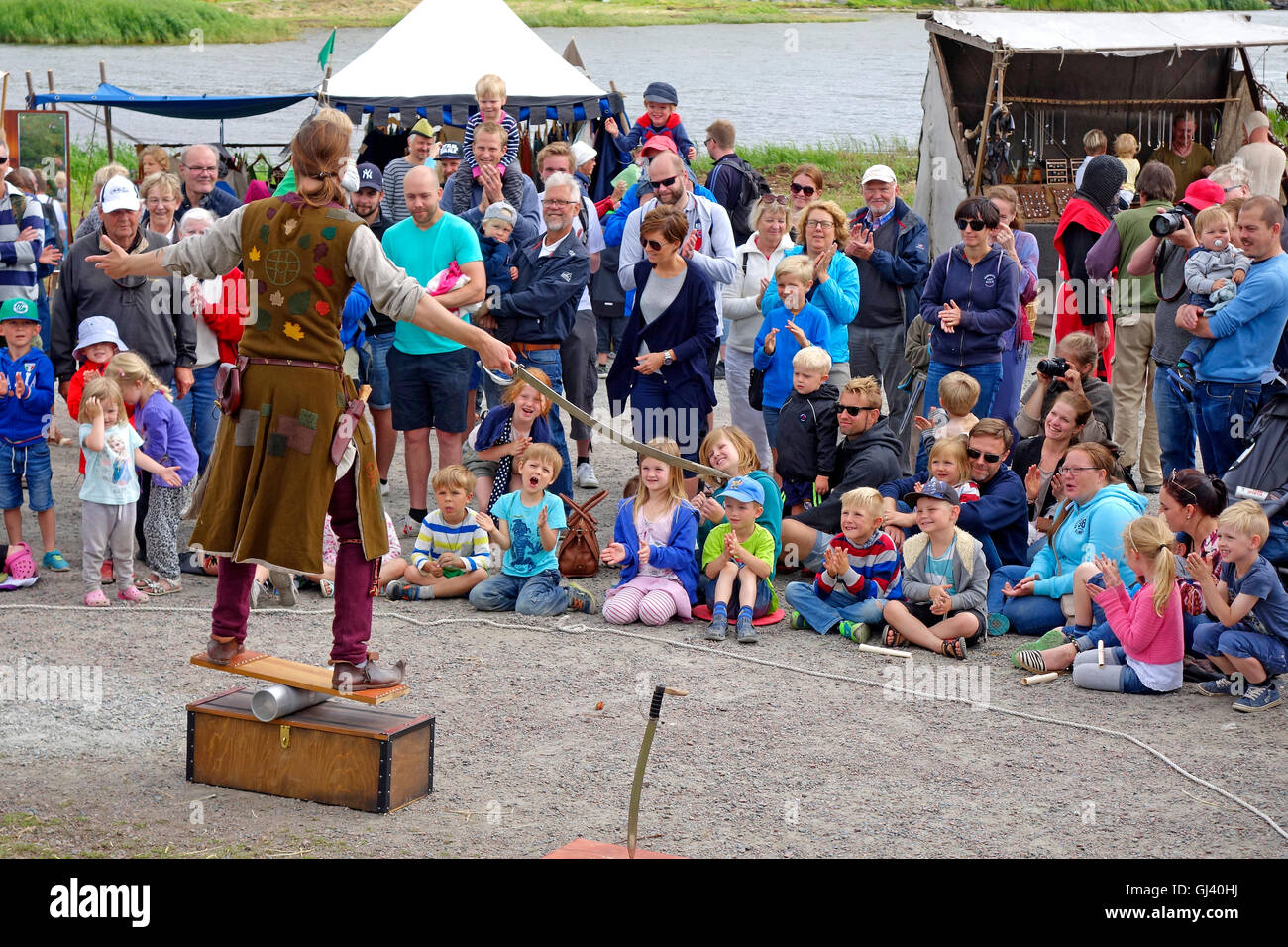 A juggler entertains audience while performing outdoors. - Stock Image