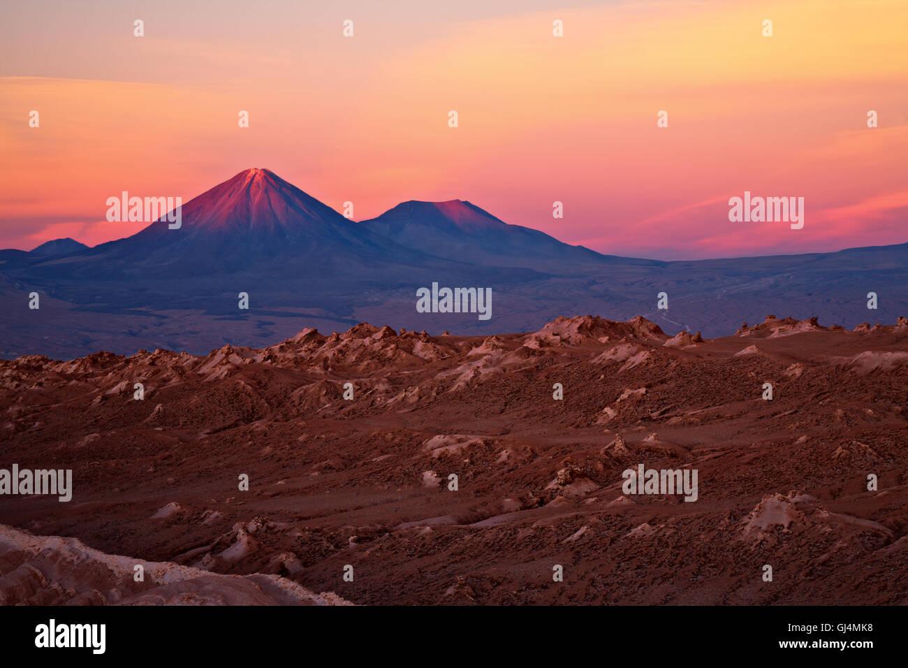 sunset over volcanoes Licancabur and Juriques and Valle de la Luna, Atacama desert, Chile - Stock Image