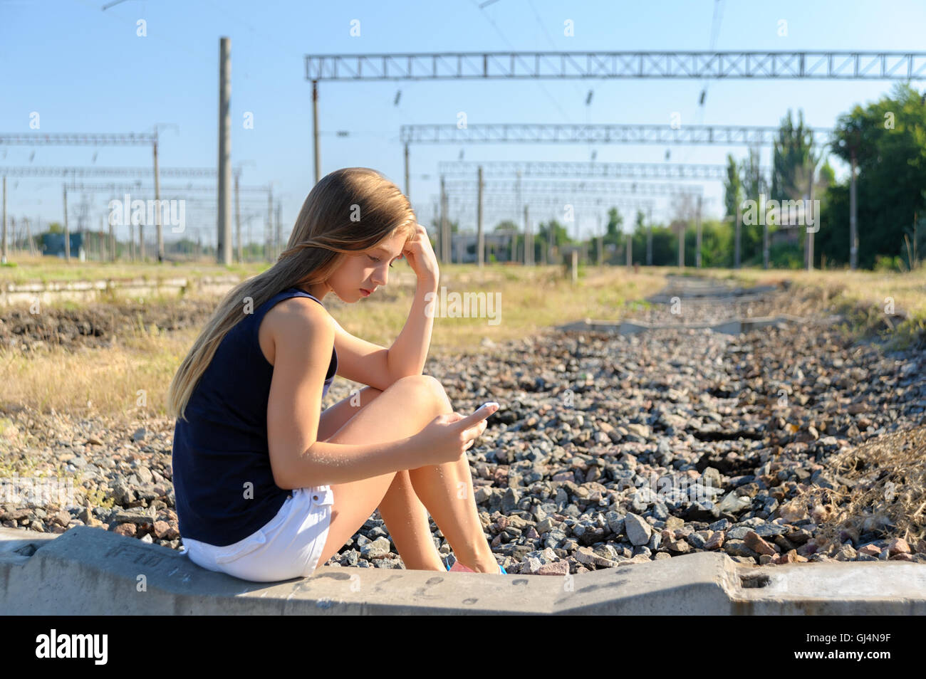 Teenager girl with mobile sitting on unfinished rail track - Stock Image
