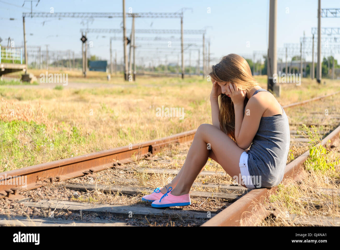 Upset teenager girl sitting on rail track in countryside - Stock Image