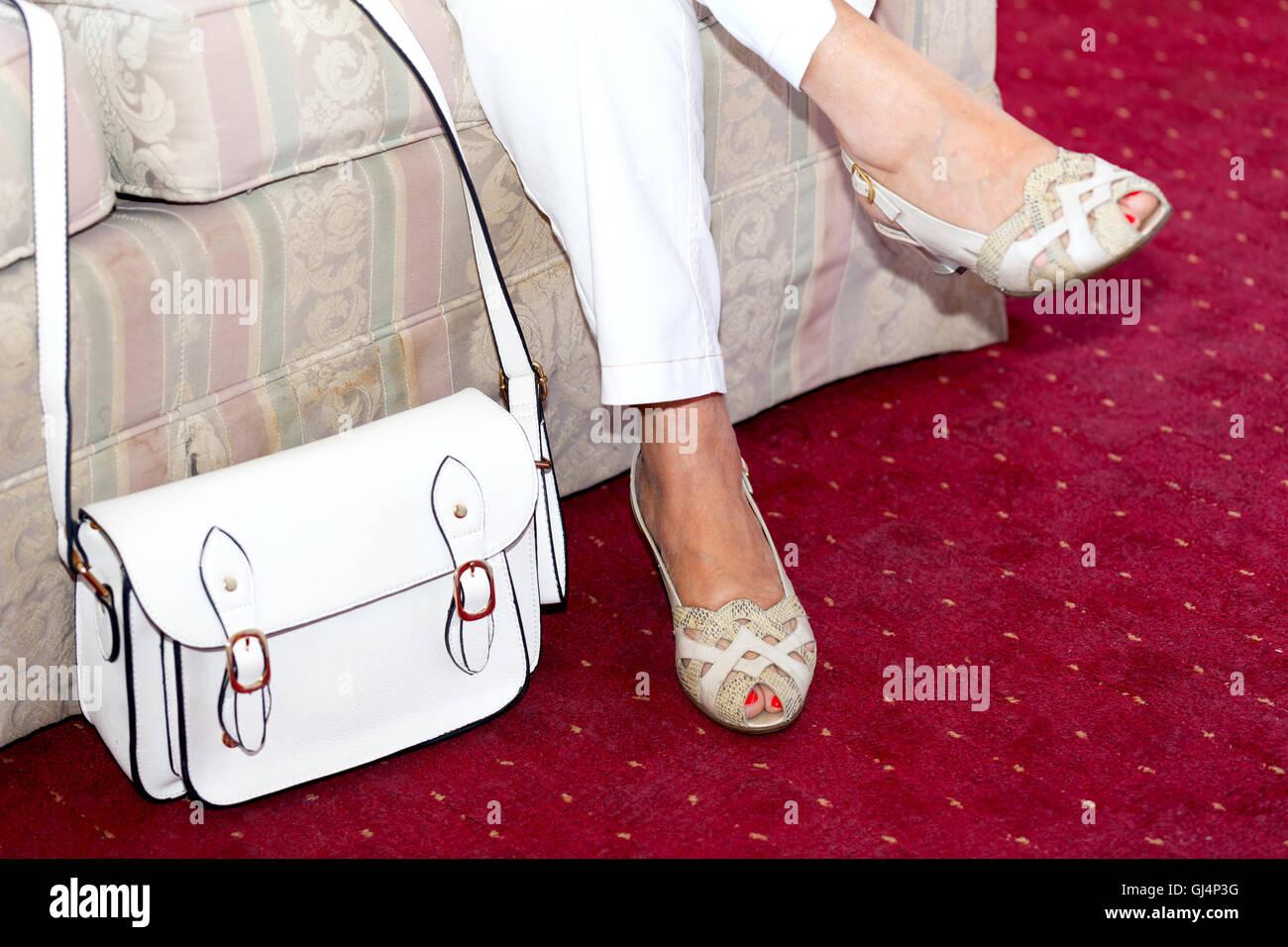 Woman sitting on sofa with white handbag - Stock Image