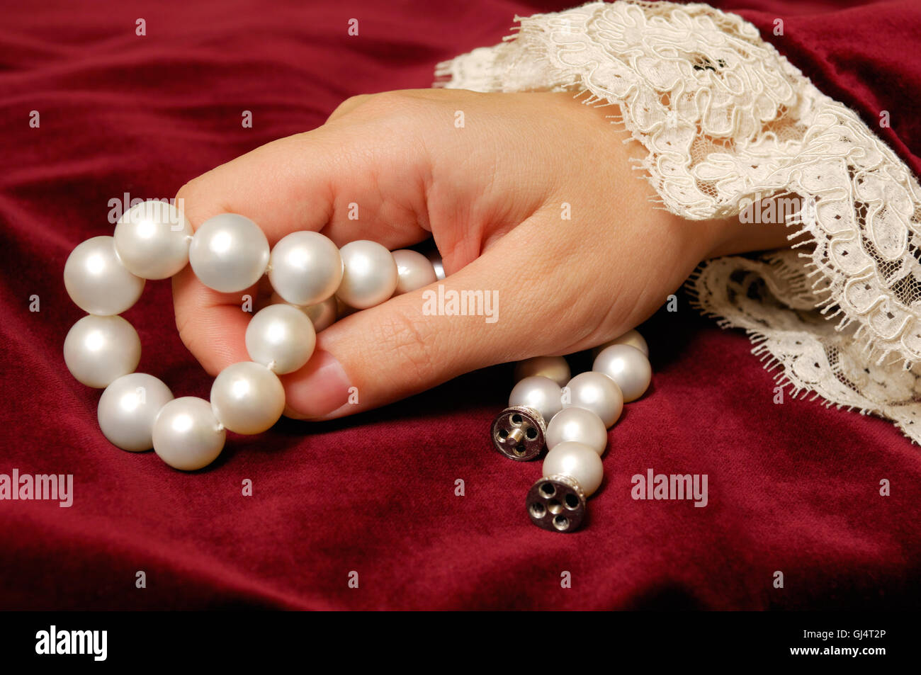 Holding a pearls necklace - Stock Image