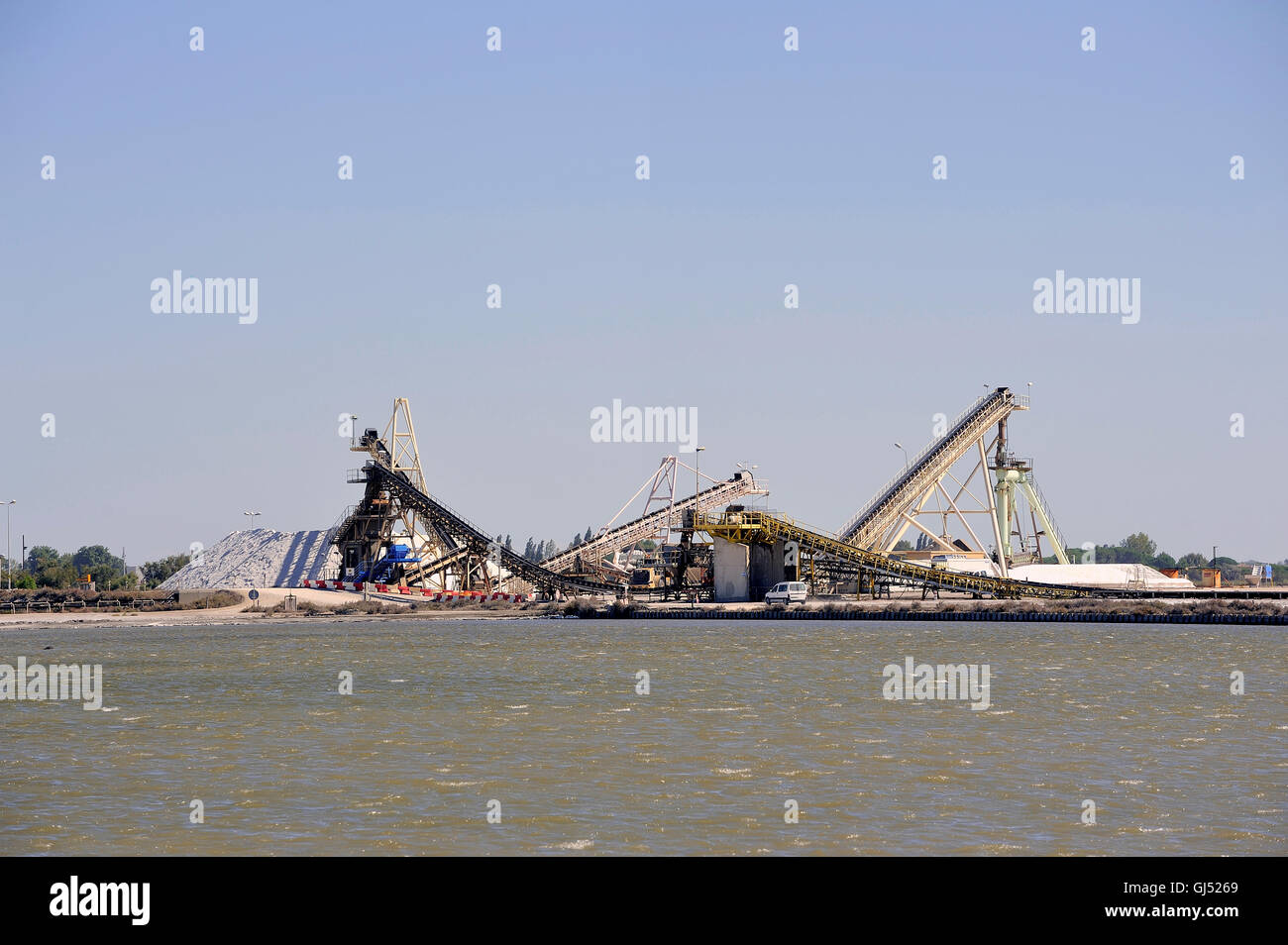 Site operating sea salt saline Aigues-Mortes with big machines and trucks working for the salt storage - Stock Image