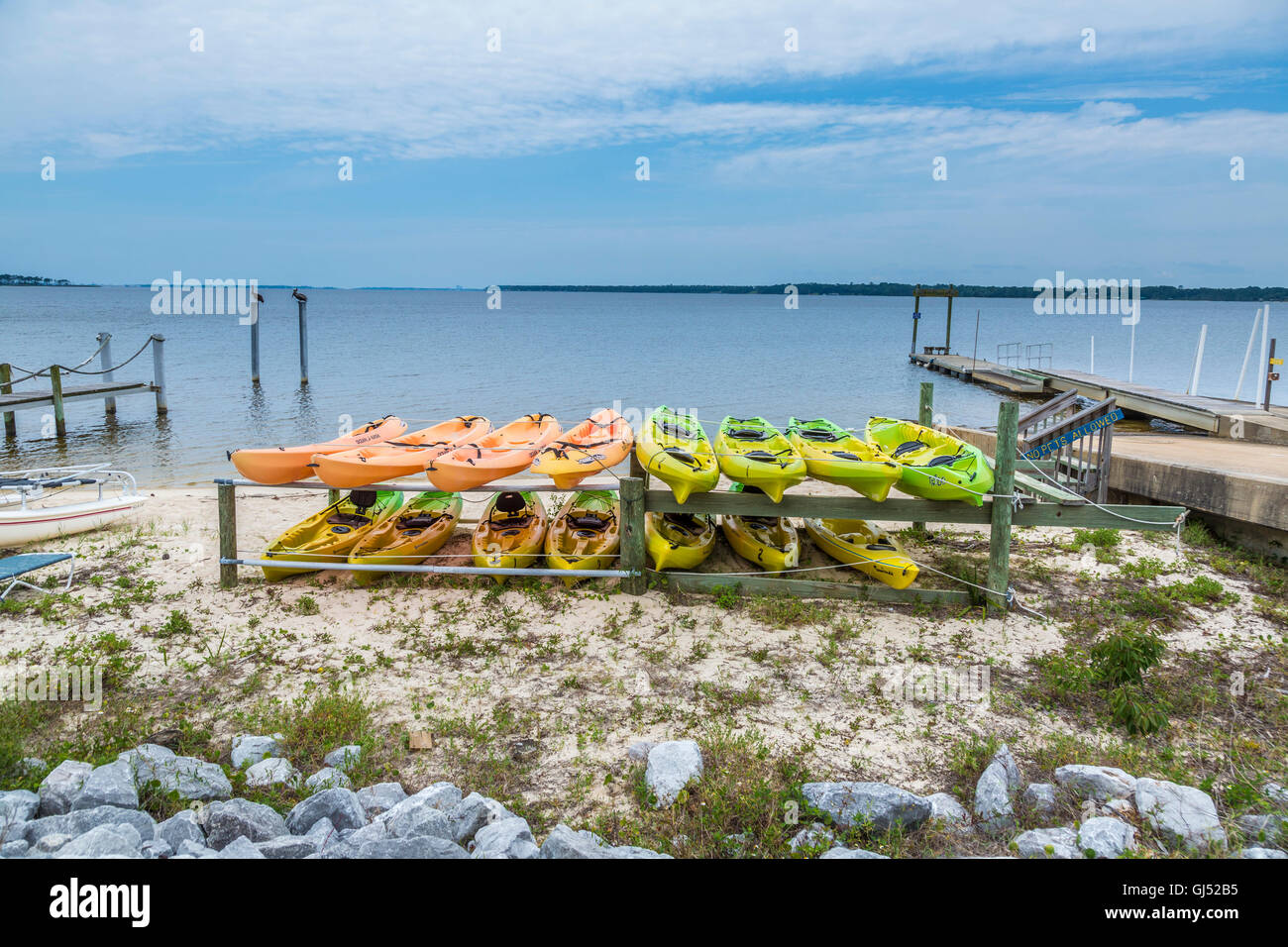 Colorful rental kayaks on rack along Perdido Bay near Perdido, Florida Stock Photo