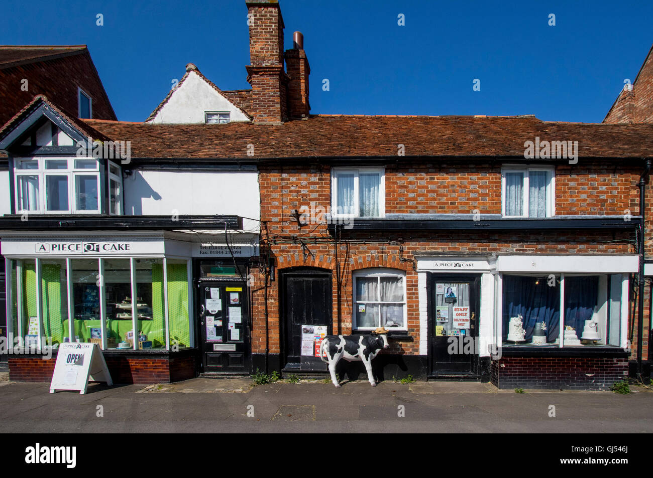 Shop with statue of cow outside in town of Thame Oxfordshire England - Stock Image