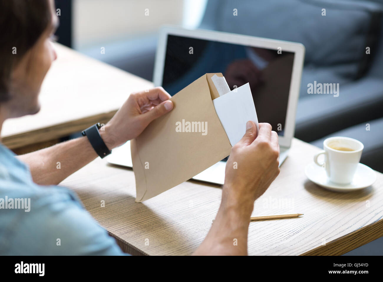 Pleasant man opening a letter - Stock Image