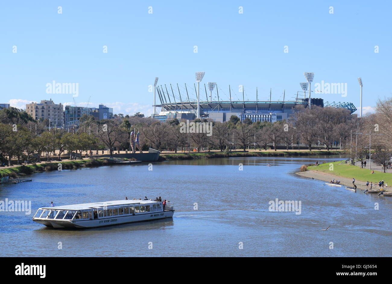 Sightseeing boat cruises in Yarra river MCG in background in Melbourne Australia. - Stock Image