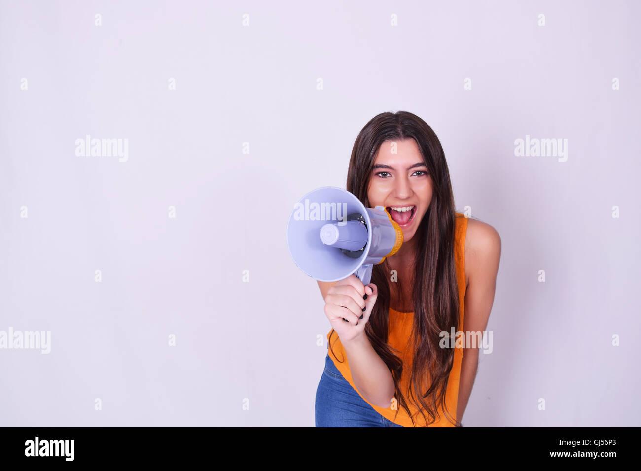 Young beautiful woman shouting through a megaphone or loudspeaker. Caucasian woman expressing. Leadership concept. - Stock Image