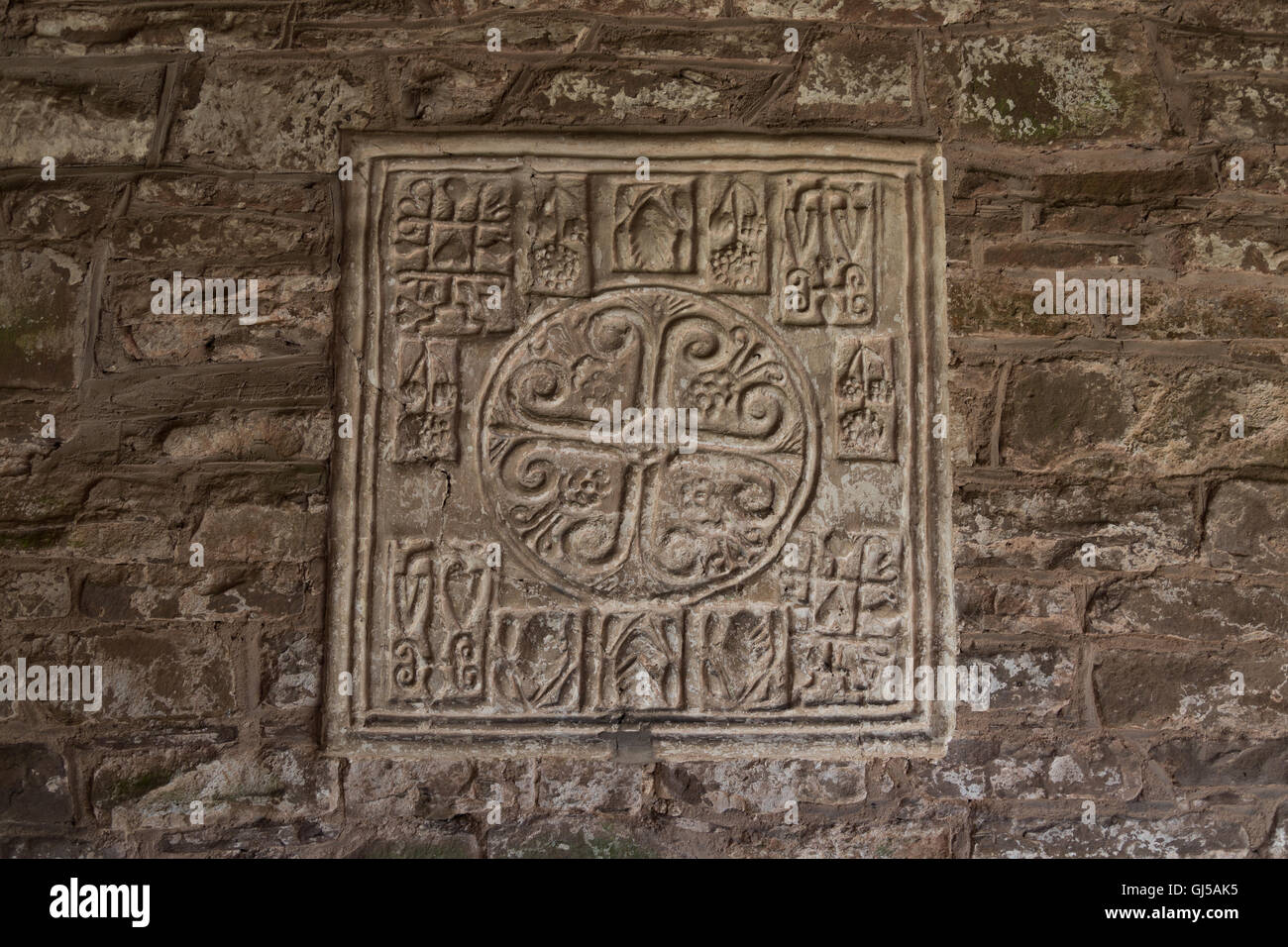 A wall tile with many symbols at St Martin's 'crooked' church in Cwmyoy, near Abergavenny. - Stock Image
