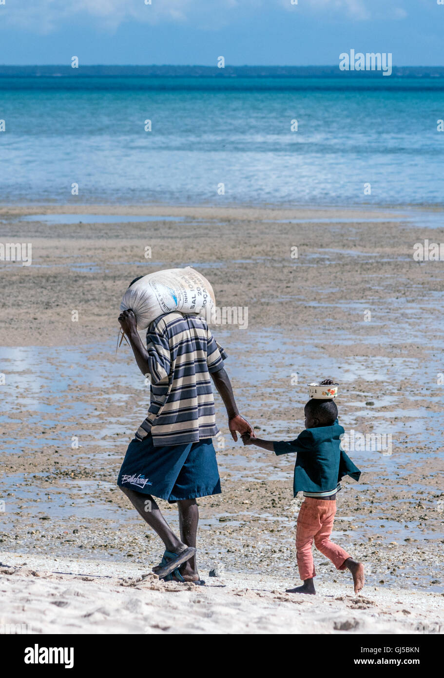 A local and his son taking home the provisions on Benguerra Island Mozambique - Stock Image