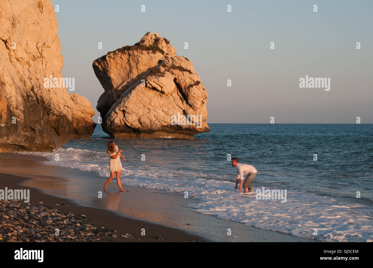 Young lovely  and happy couple playing with water at the Aphrodite birth place beach at Paphos, Cyprus - Stock Image