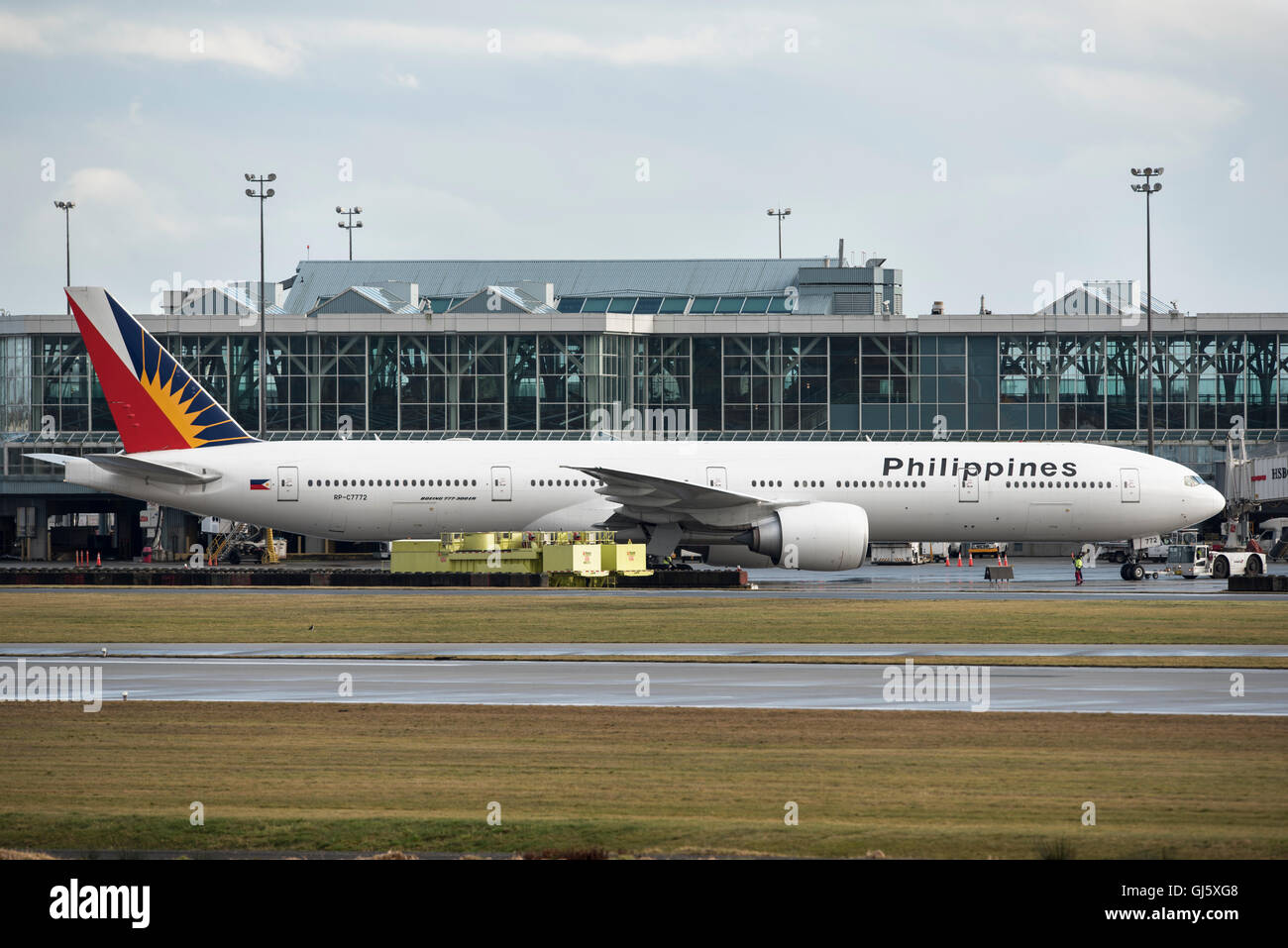 Philippines airline Boeing 777-300 taxiing to Vancouver International airport terminal. - Stock Image