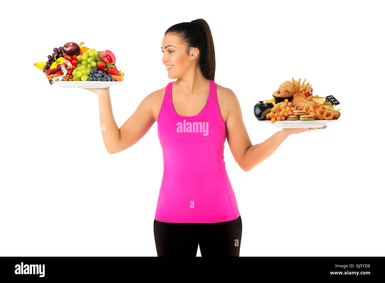 Healthy  or unhealthy lifestyle concept young woman holding two plates of food one unhealthy  but looking at healthy - Stock Image