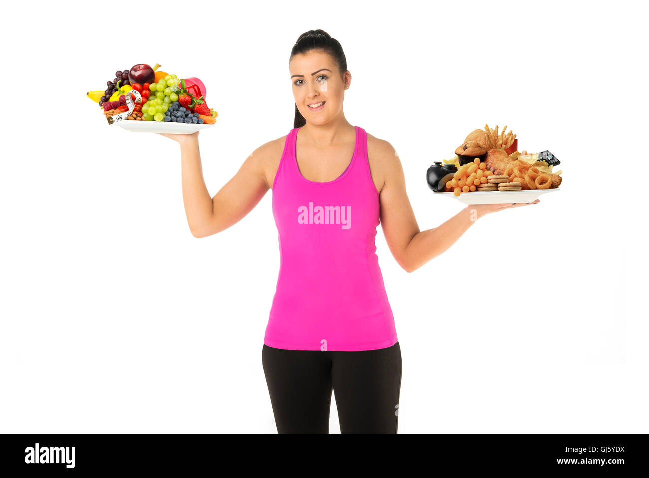 Healthy  or unhealthy lifestyle concept young woman holding two plates of food one unhealthy the other healthy choose - Stock Image