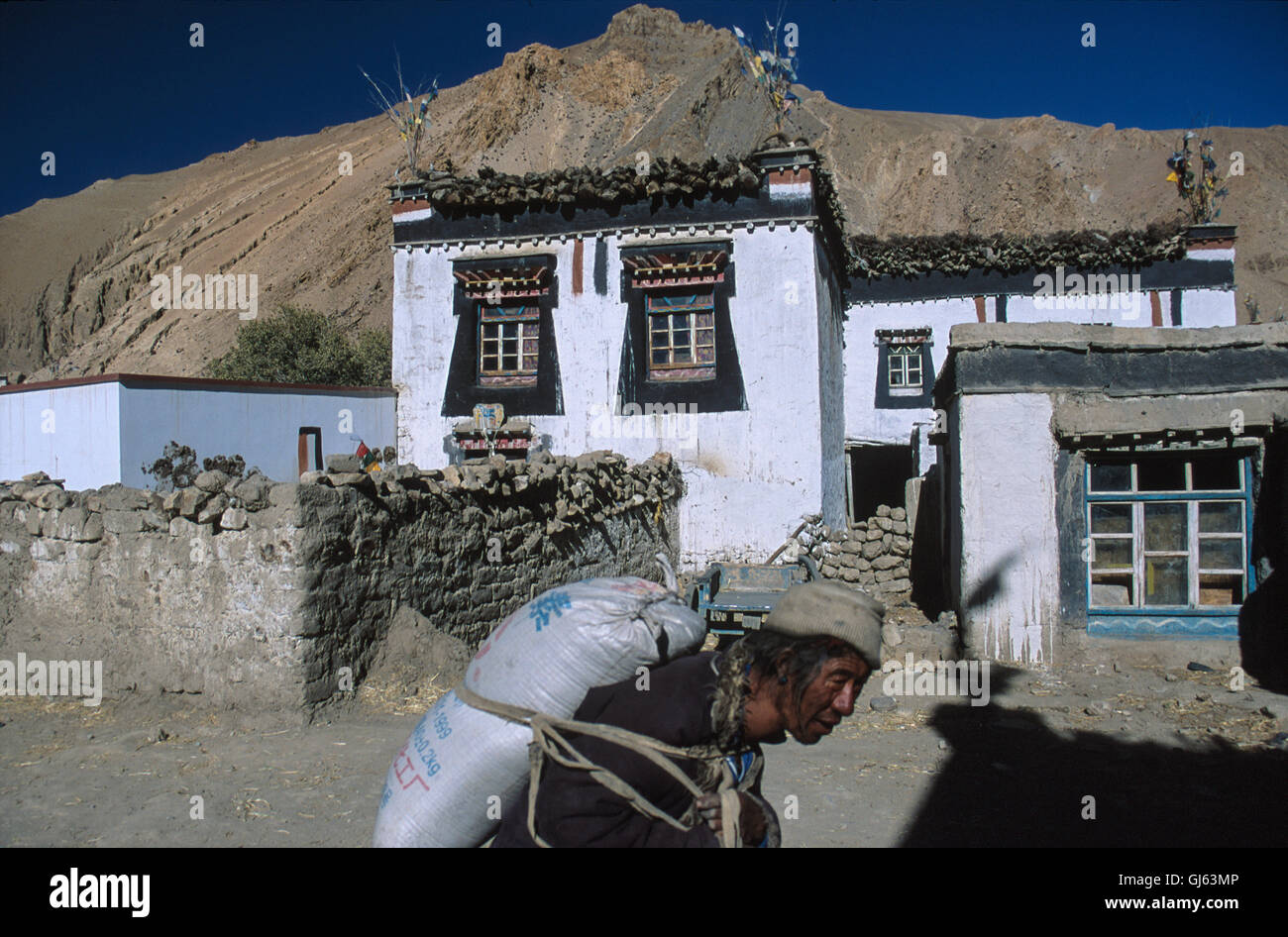 Local passing typical Tibetan home with the commonly used brown, white and black colours at village of Phadhruchi, - Stock Image
