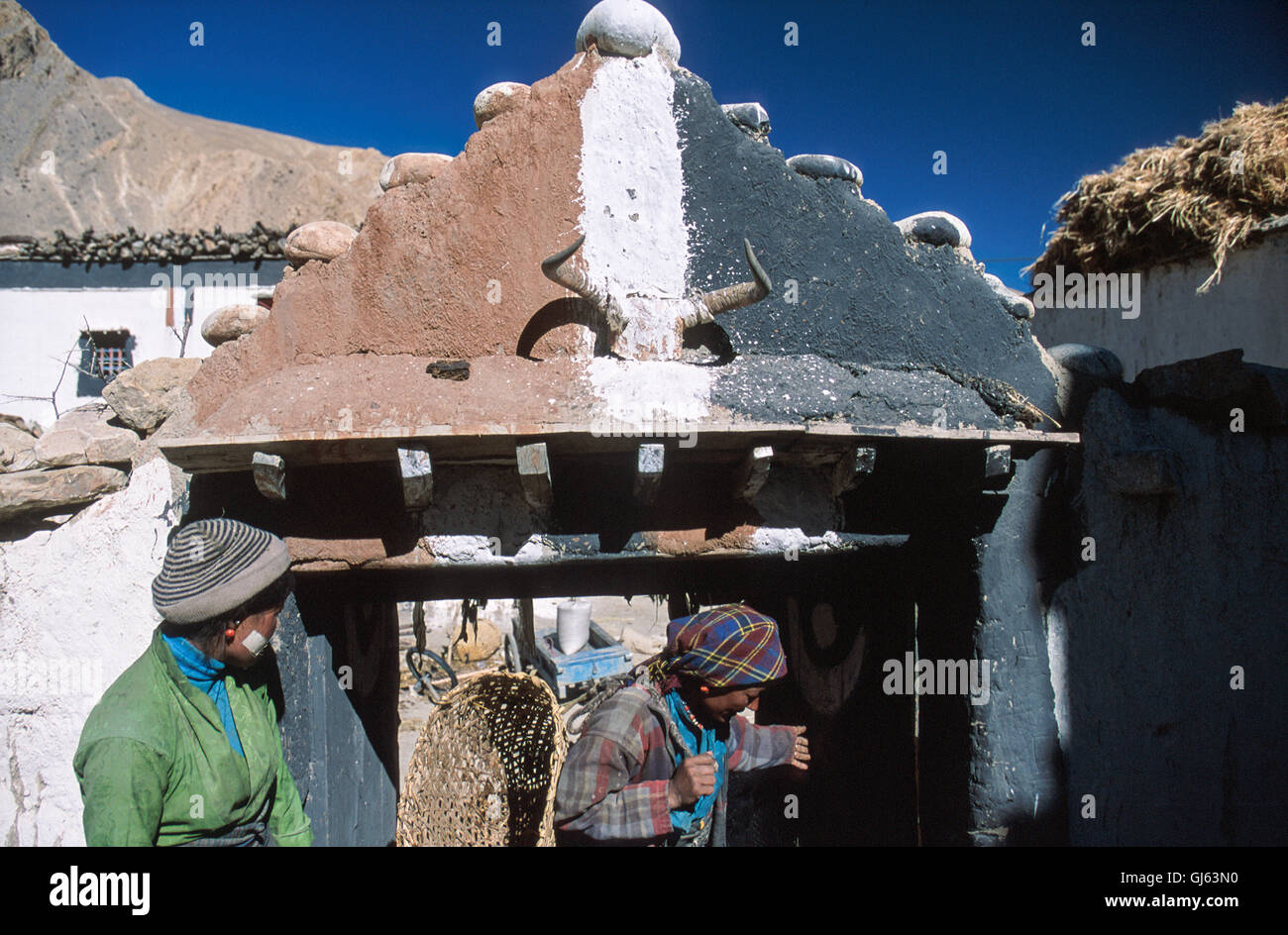 155 Locals at entrance to this typical Tibetan home complete with horned yak skull with the commonly used brown, - Stock Image
