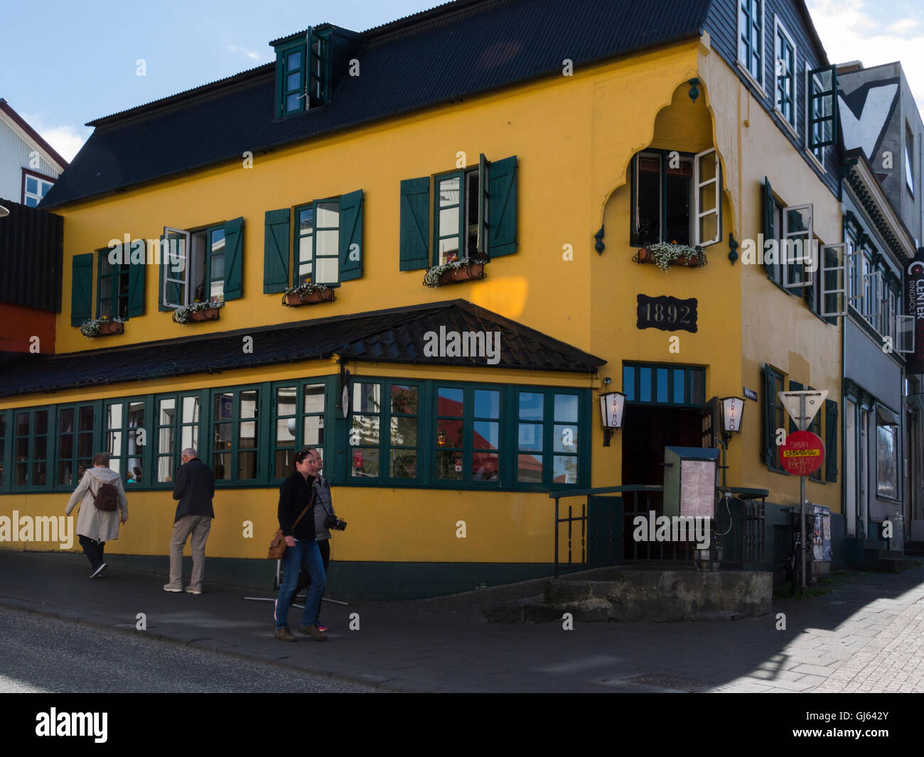 Italian restaurant in yellow building with green shuttered windows dating from 1892 in historic city centre Reykjavik - Stock Image