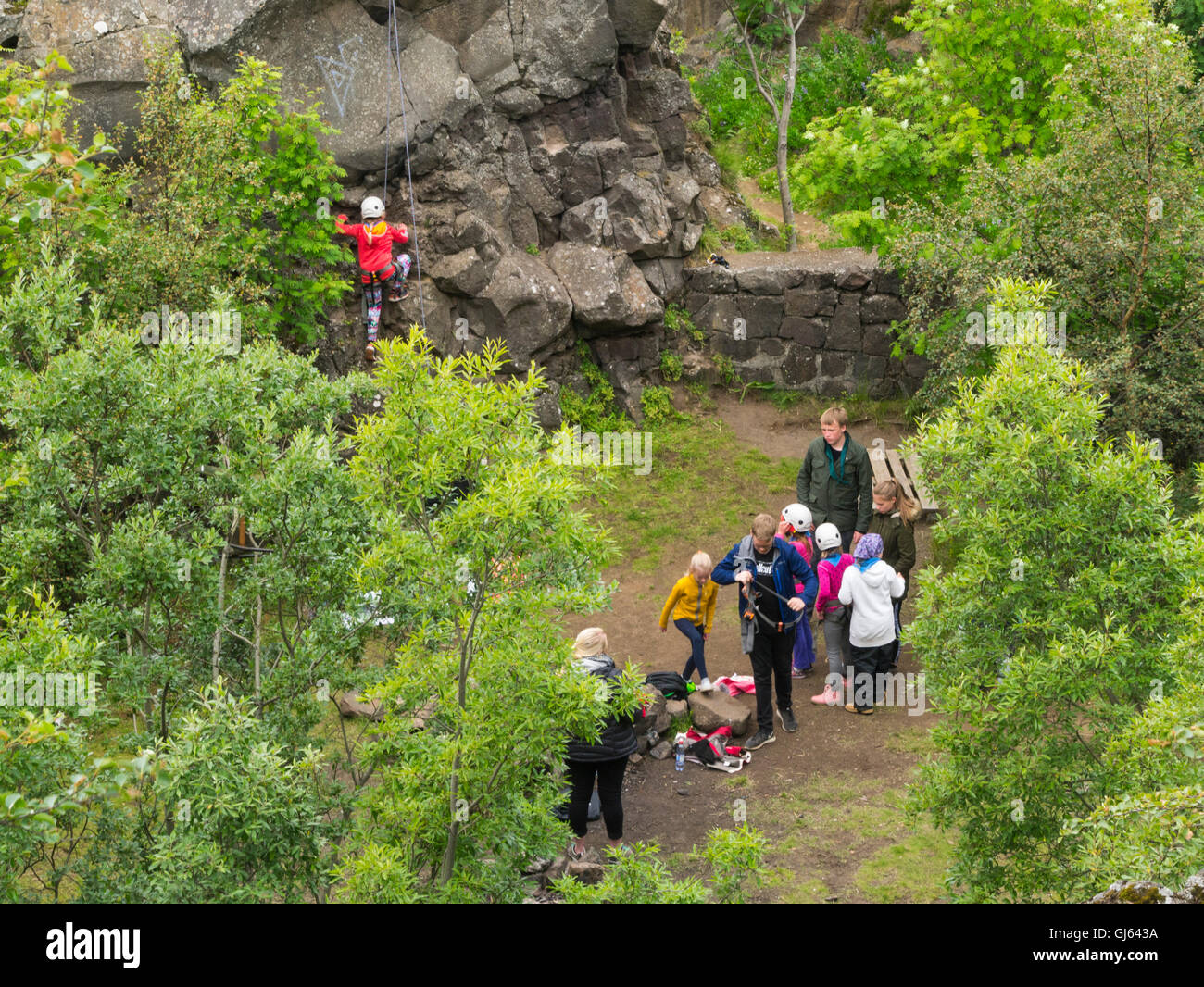 Group of schoolchildren learning to rock climb little girl holding rope on rockface Iceland teacher helping group - Stock Image