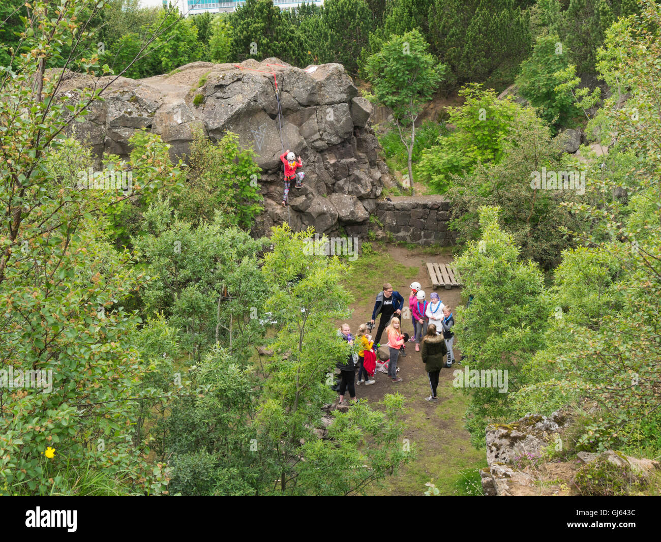 Group of schoolchildren learning to  rock climb  little girl holding rope on rockface  Iceland - Stock Image