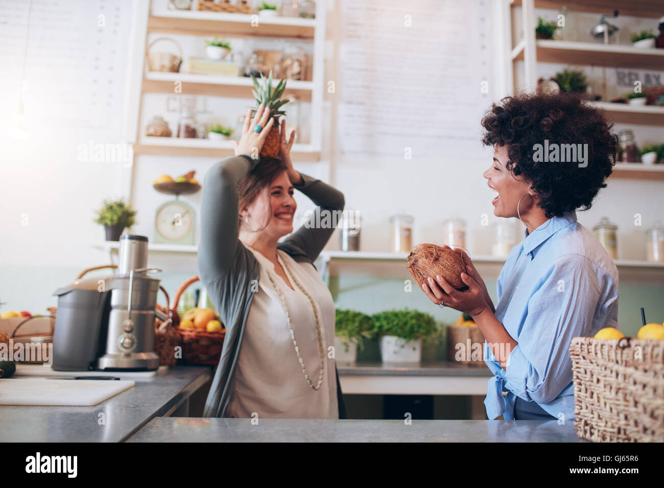 Juice bar employees playing with fruits at work. Young women holding coconut and pineapple while standing at bar - Stock Image