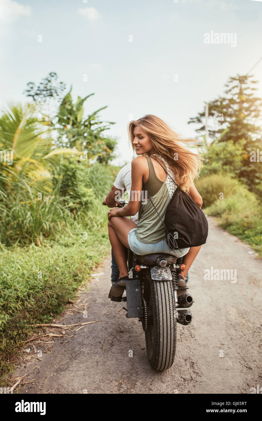 Rear view shot of young couple riding motorbike on dirt road. Beautiful young woman sitting on back of her boyfriend - Stock Image