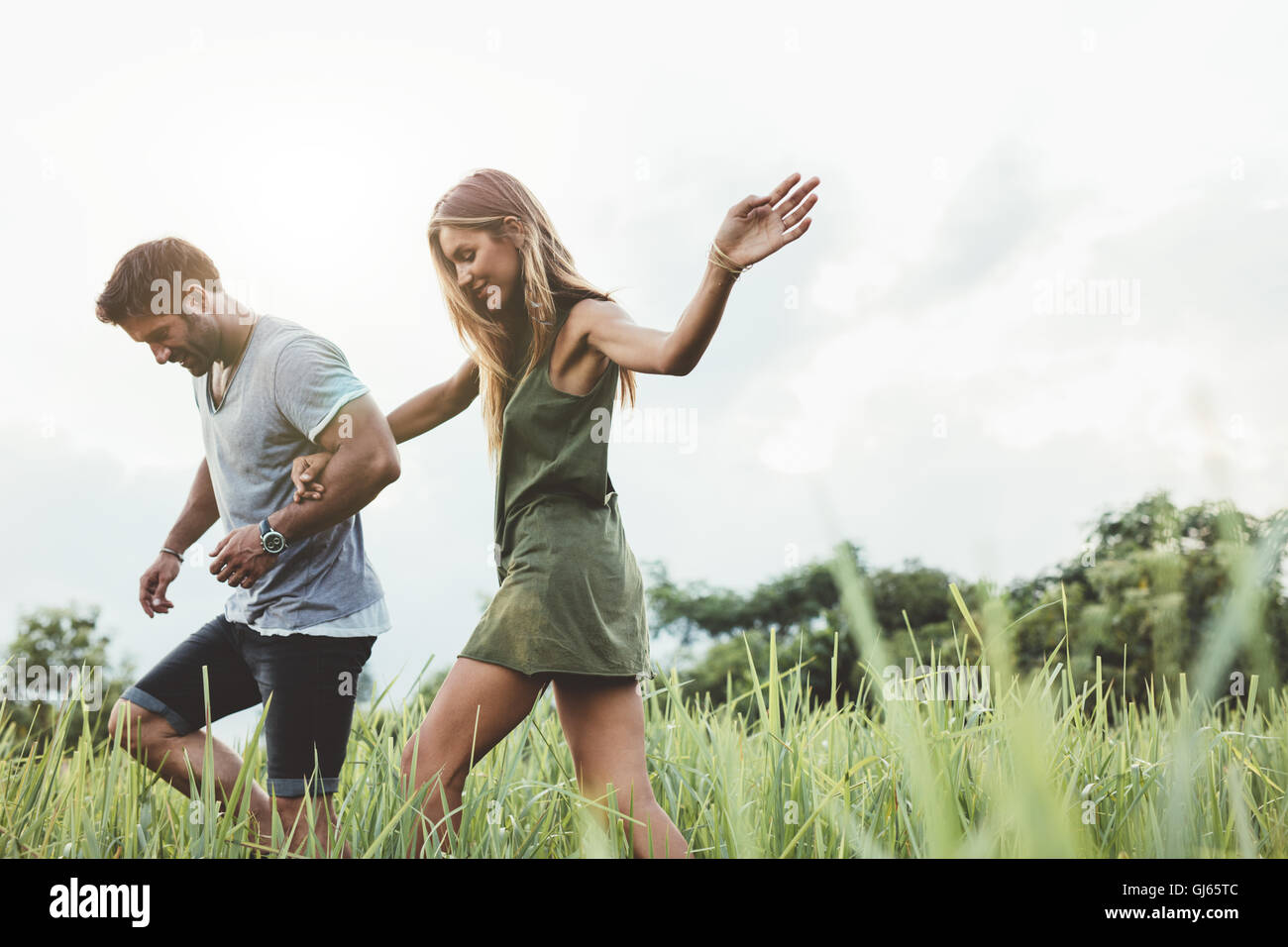 Outdoor shot of young couple walking through meadow hand in hand. Man and woman talking walk through grass field Stock Photo