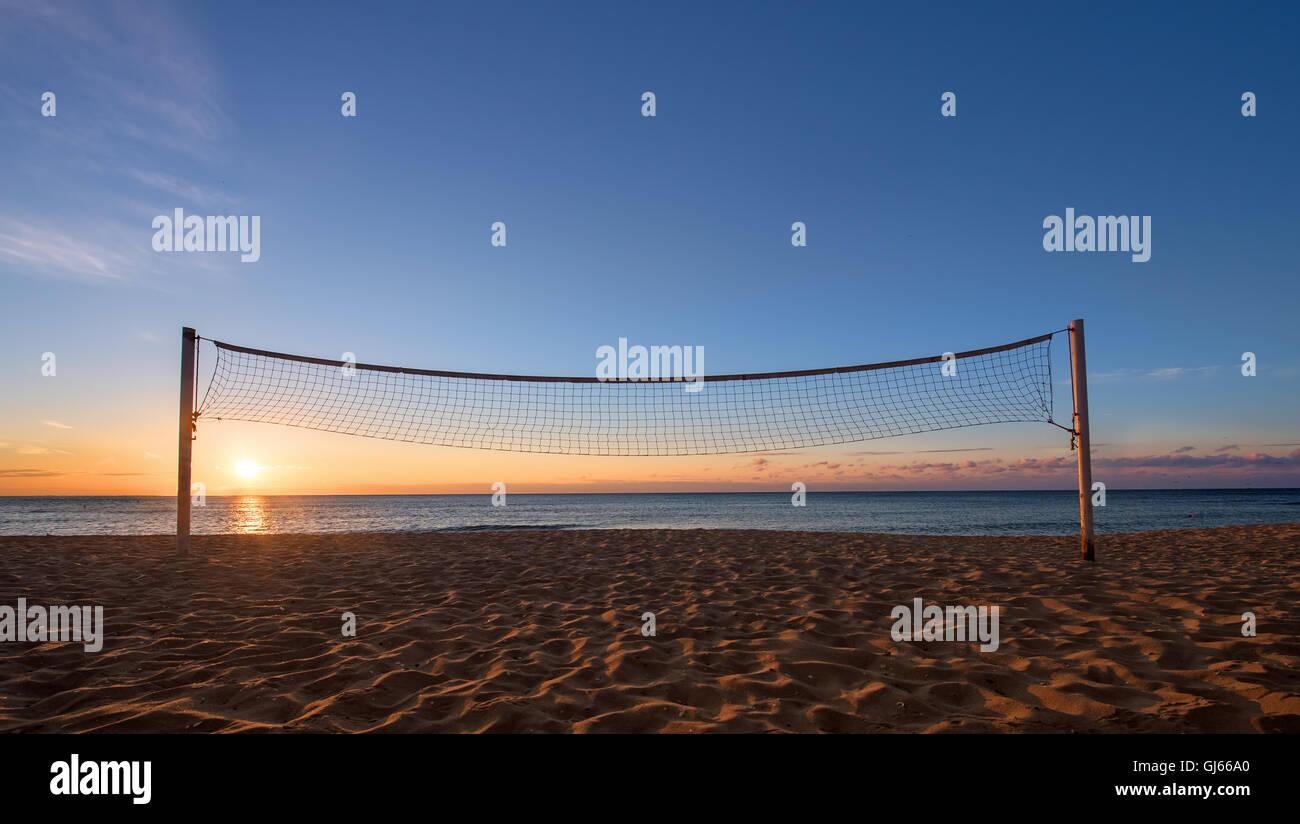 Sillhouette of a volleyball net against sunrise on the beach - Stock Image