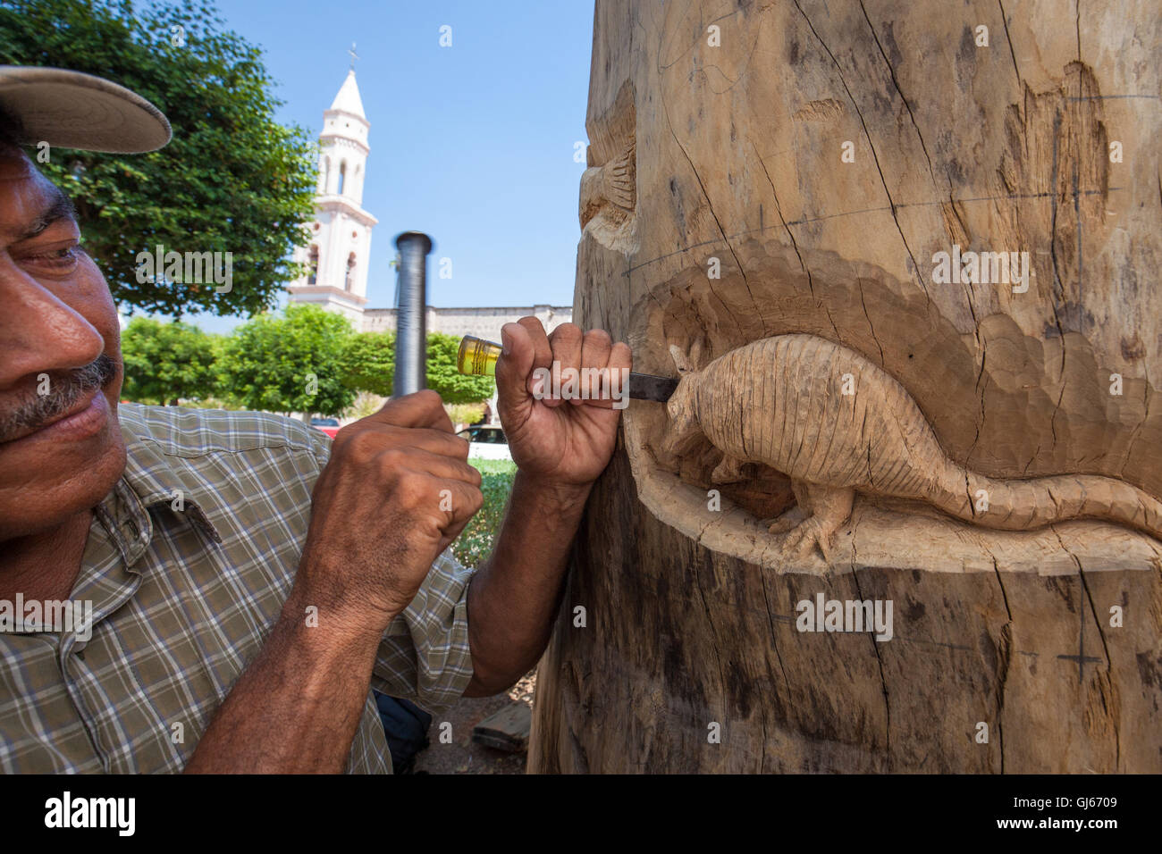 Artisan Jesus Ramos Cota works on a carving in the plaza of el Fuerte, Sinaloa, Mexico. - Stock Image