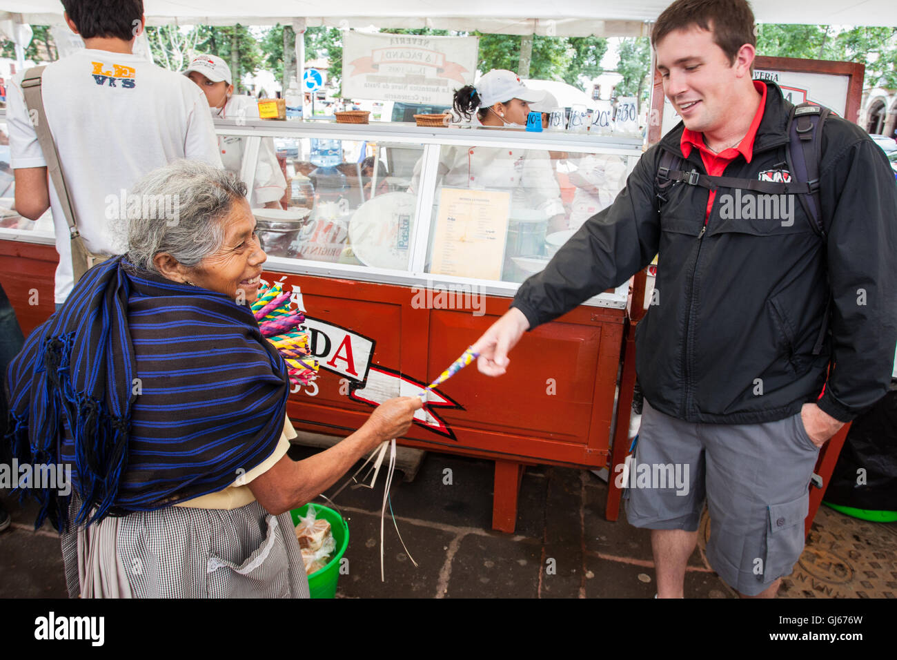 A Purepecha saleswoman demonstrates the use of the atrapa novios (boyfriend catchers) she is selling in Patzcuaro, - Stock Image