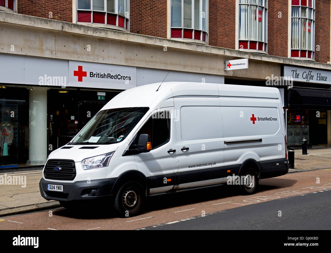 Delivery van parked outside Red Cross charity shop, England UK - Stock Image