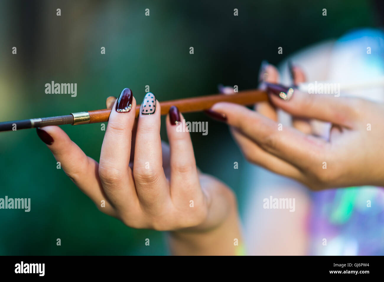 Beautiful hand of a young woman with brown manicure mouthpiece with cigarette - Stock Image