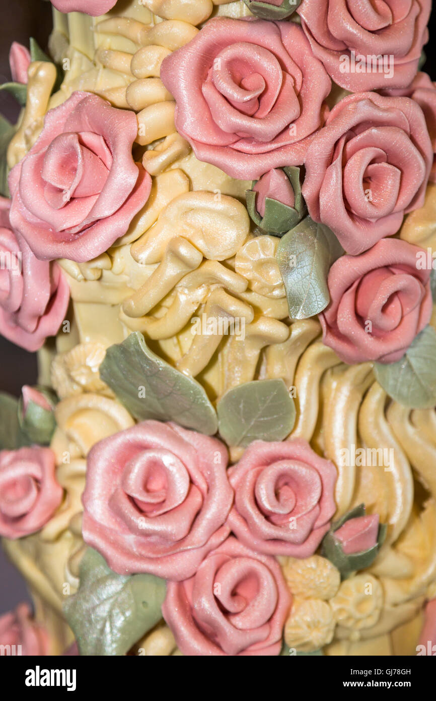 Detail of an elaborate bespoke chocolate wedding cake with chocolate pink roses and dinosaur bones and fossil spine - Stock Image