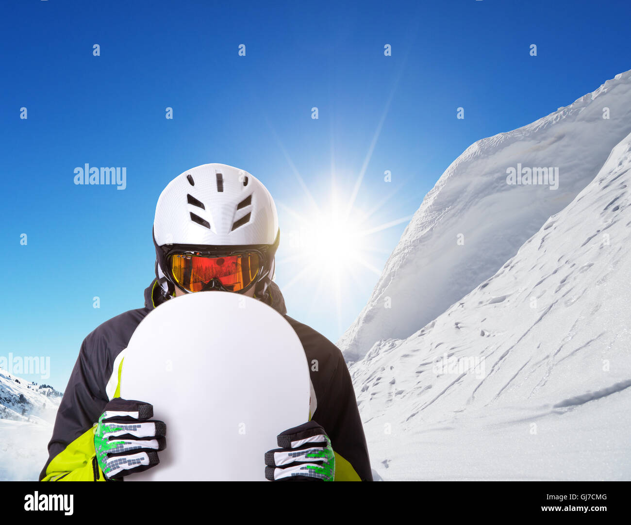 Snowboarder holding his snowboard off piste, beautiful winter landscape panorama on background - Stock Image