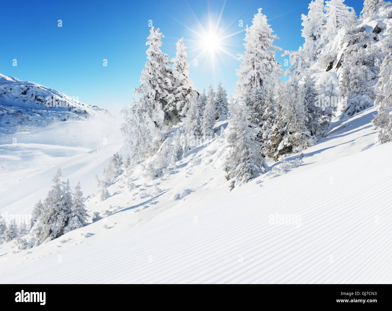Beautiful winter landscape with ideal piste. Blue sky with sun light and high Alpine mountains on background - Stock Image