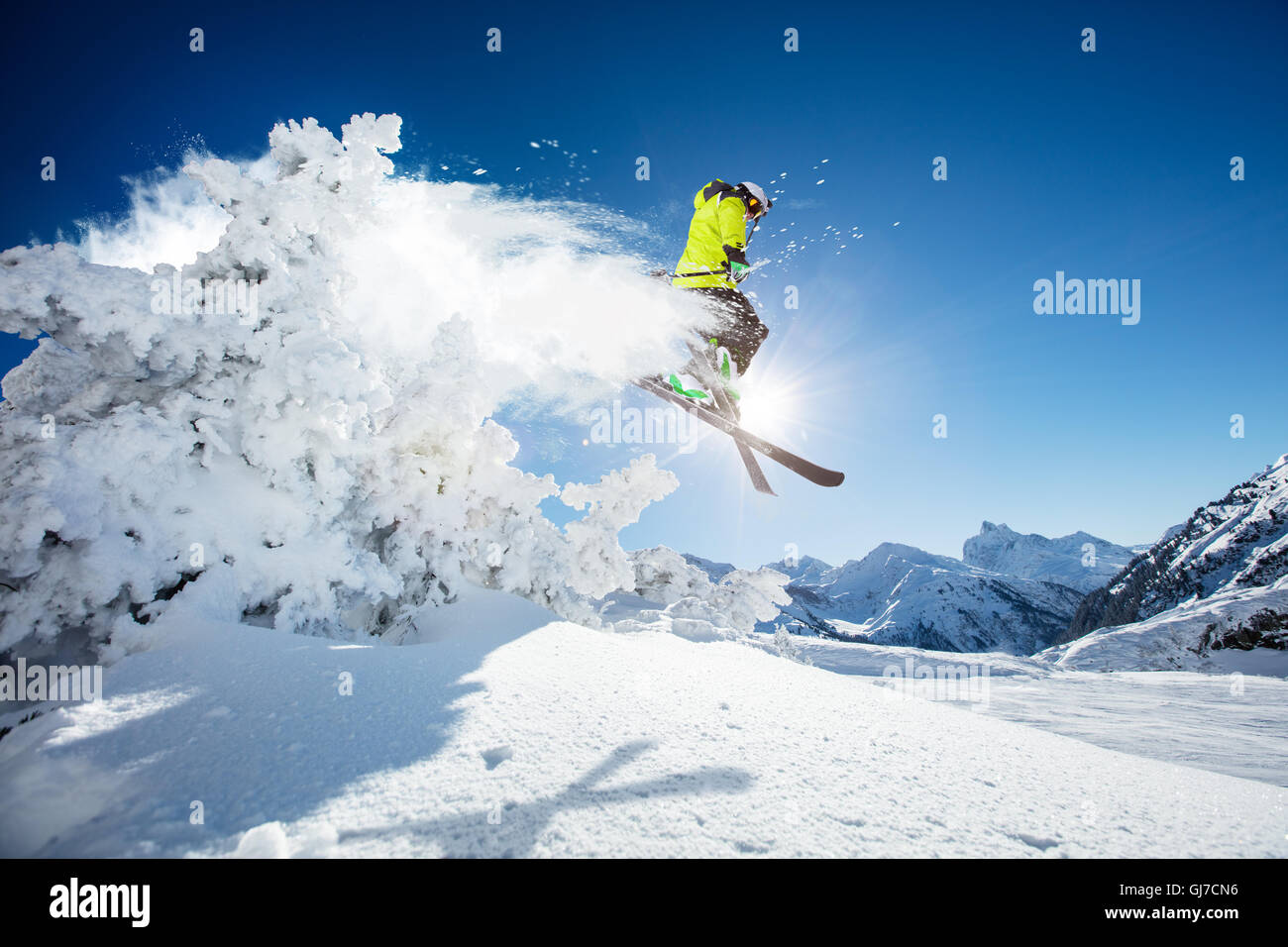 Skier at jump in Alpine mountains in beautiful sunny day. Copyspace for text - Stock Image